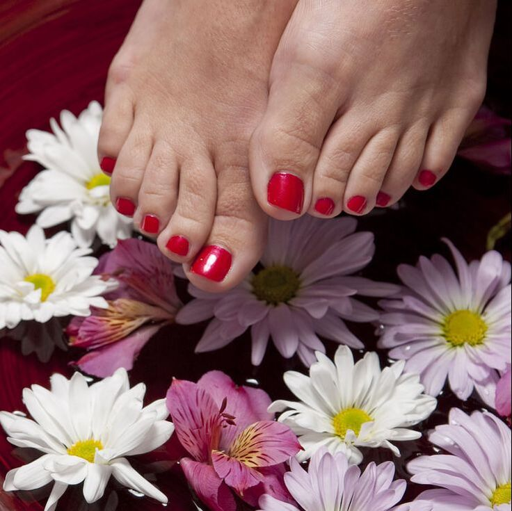 Red toe nails over flowers