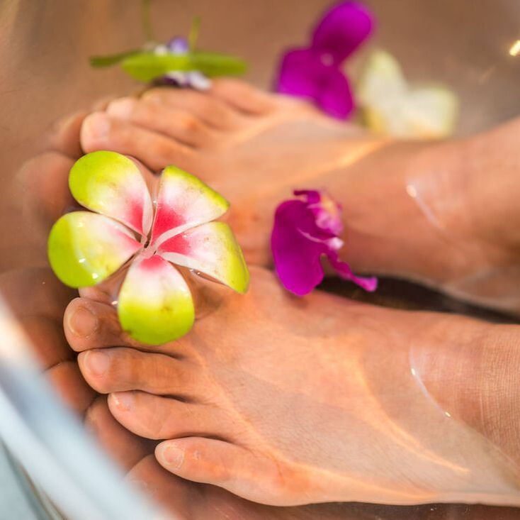 Feet soaking in flowers and foot bath